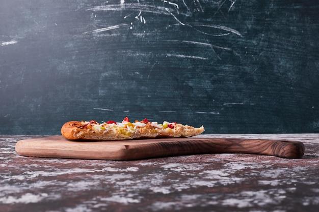 Een stuk pizza op blauw.