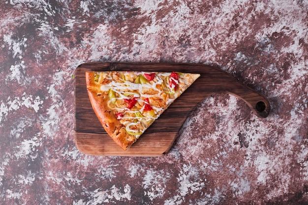 Een stuk pizza op een houten bord, bovenaanzicht