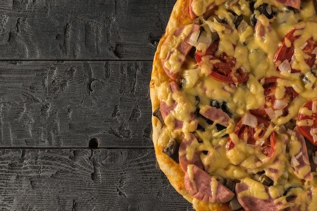 Een stuk pizza op een zwarte houten tafel. traditionele italiaanse keuken. het uitzicht vanaf de top.
