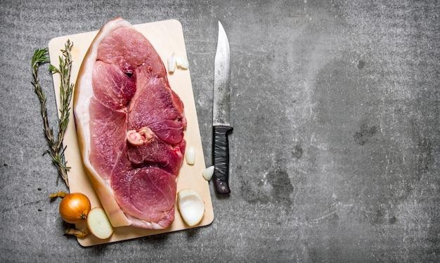 Een stuk rauw varkensvlees met kruiden en een snijmes. op de stenen tafel. vrije ruimte voor tekst. bovenaanzicht