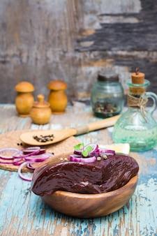 Een stuk rauwe runderlever in een kom met ingrediënten voor het koken op een houten tafel
