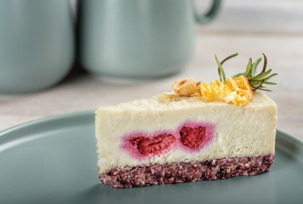 Een stuk rauwkost cheesecake met aardbeien op een grijze plaat.