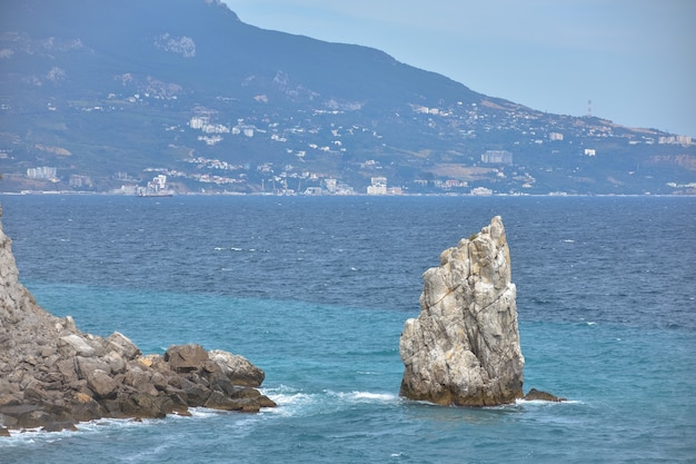 Een stuk rots bij de zee bij de kust, zicht op de kustrotsen bij het kasteel swallow's nest op de krim, een vrijstaand groot stuk rots in het midden, kustlijn links, zeezicht