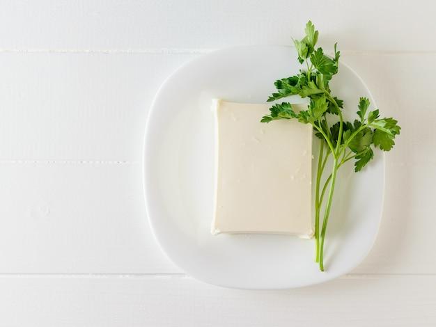 Een stuk servische kaas met een klein blad van peterselie op een witte tafel. het uitzicht vanaf de top. zuivel product. plat liggen.