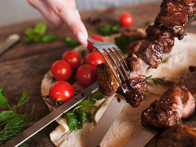Een stuk shish-kebab wordt van de spies gehaald.
