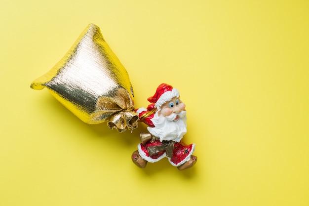 Een stuk speelgoed kerstman met een gouden zak van giften op geel met copyspace. het concept van kerstmis nieuwjaar.