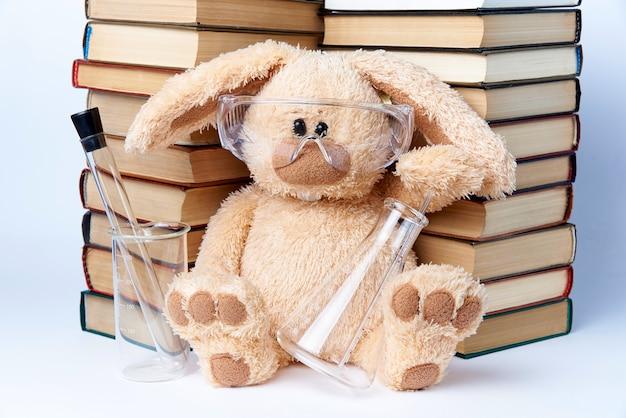 Een stuk speelgoed konijn in beschermende glazen met bekers en flessen zit dichtbij een stapel boeken.