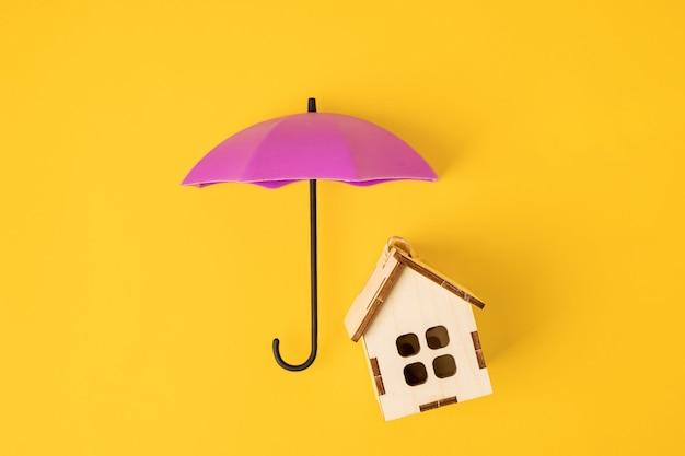 Een stuk speelgoed paraplu over een houten huis op een gele achtergrond. een symbool van zorg en betrouwbaarheid