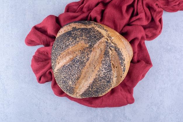Een stuk stof onder een met zwart sesam bedekt brood op een marmeren oppervlak