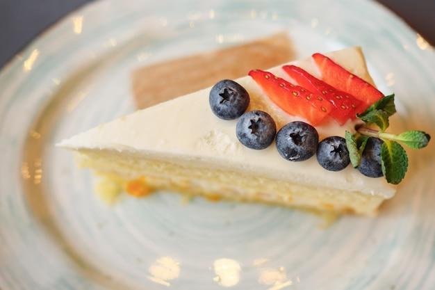 Een stuk taart met aardbei en bosbes op plaat, selectieve aandacht. bovenaanzicht