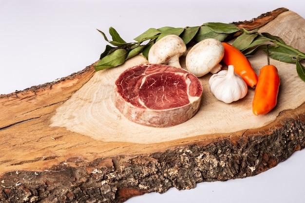 Een stuk vlees, champignons en chilis op een houten tafel