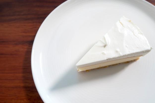 Een stuk witte cake op witte schotel. bovenaanzicht.