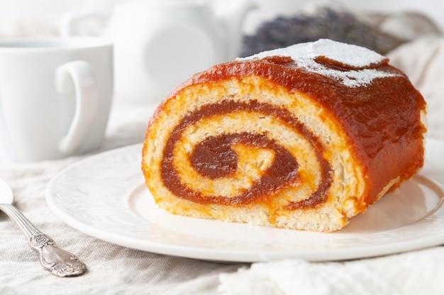 Een stuk zelfgemaakte biscuit met appeljam op een witte plaat op de achtergrond staat een witte theepot en een mok close-up