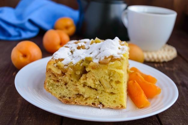 Een stuk zelfgemaakte cake met schijfjes appel en abrikoos, decoratieve poedersuiker.