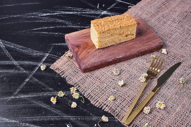 Een stuk zelfgemaakte honingcake op een houten bord naast gouden bestek.