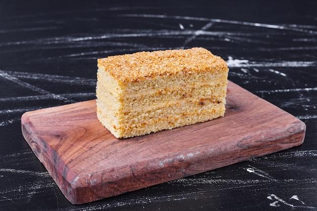 Een stuk zelfgemaakte honingcake op een houten bord.