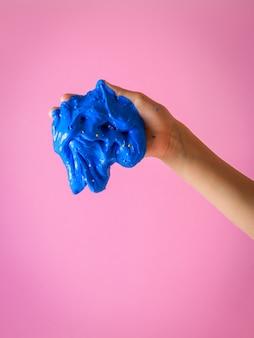Een stukje blauw slijm in de hand van een kind op een rode achtergrond.