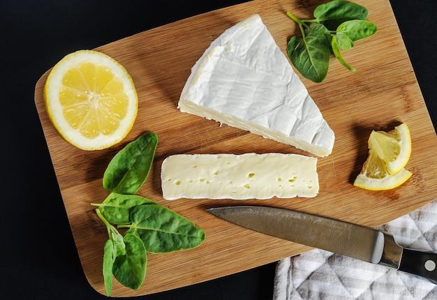 Een stukje brie kaas, citroen, mes en spinazie liggen op de snijplank.