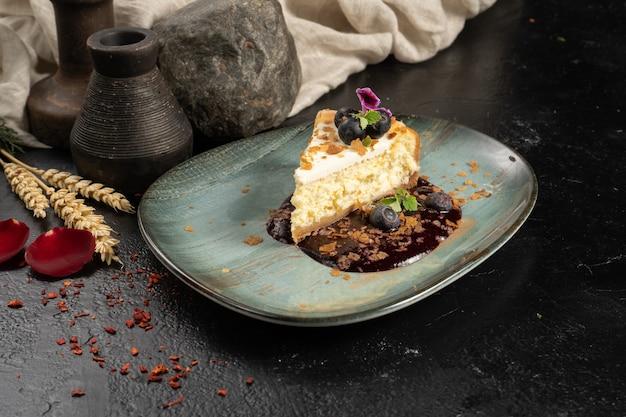 Een stukje cheesecake met bosbessen en bessensaus op een dessertbord
