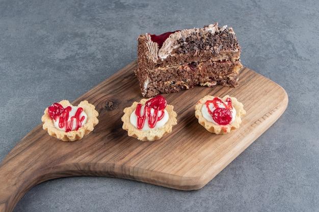 Een stukje lekkere cake en mini cupcakes op een houten bord