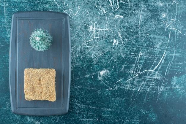 Een stukje lekkere cake met kleine kerstboom op een donkere plaat. hoge kwaliteit foto