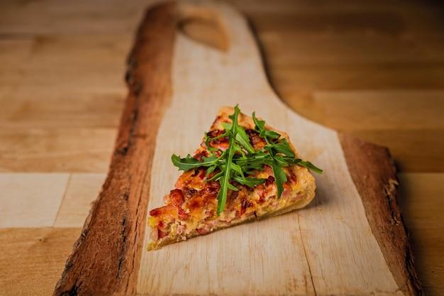 Een stukje quiche met kaas, ham en rucola op een houten bord