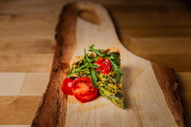 Een stukje quiche met tomaten, spinazie en rucola op een houten bord