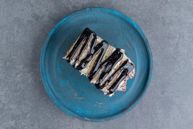 Een stukje romige cake met chocolade op een blauw bord