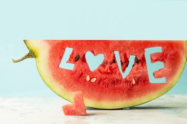 Een stukje watermeloenwereld liefde, hart tegen de blauwe kopie ruimte. watermeloen met een gat in de vorm van een hart. zomer, watermeloenminnaar, het concept van de de zomerverkoop.