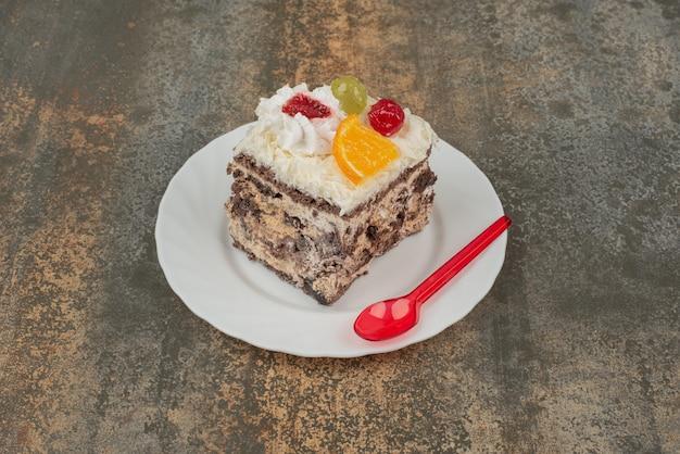 Een stukje zoete cake met rode lepel op een witte plaat