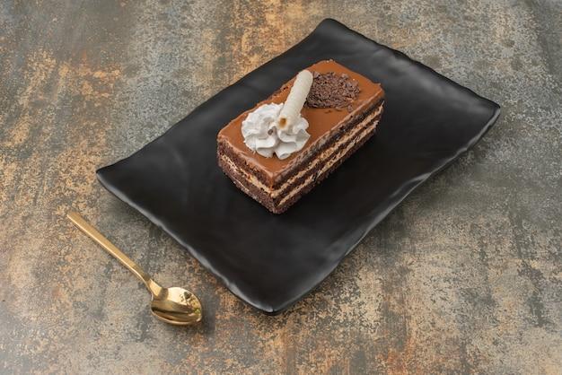 Een stukje zoete taart met gouden lepel op een donkere plaat