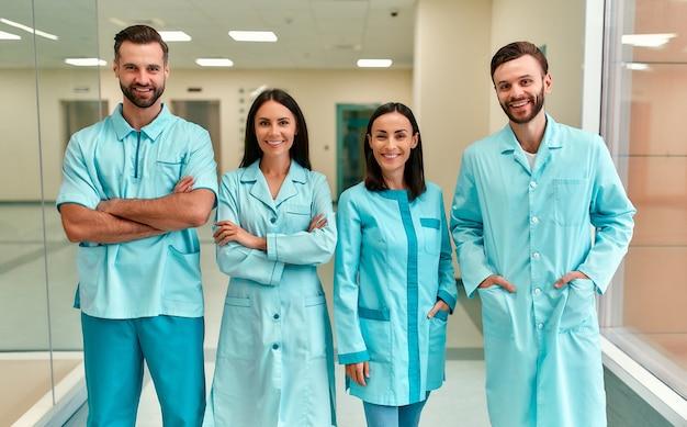 Een succesvol glimlachend team van jonge artsen of stagiaires in blauwe medische uniformen staat in de gang van de kliniek.
