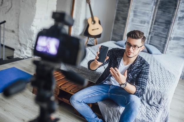 Een succesvolle blogger praat over een nieuwe mobiele telefoon in zijn kamer