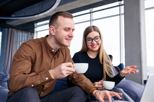Een succesvolle jonge vrouw manager met haar baas zit met een laptop op een gestoffeerde fauteuil bij het panoramische raam en drinkt koffie. zakenvrouw en man werken aan een nieuw project