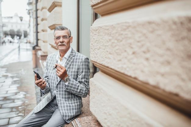 Een succesvolle oude man van de zomerdag met cubaanse sigaret die naar de camera kijkt