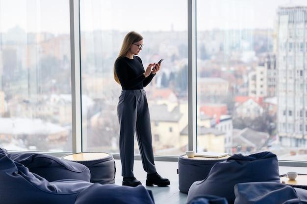 Een succesvolle vrouwelijke manager in haar eigen kantoor met grote ramen staat en kijkt naar de stad. zakenvrouw met bril op de achtergrond van grote ramen