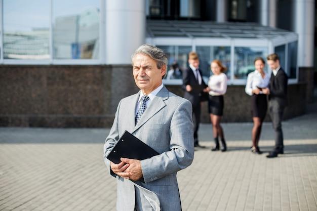 Een succesvolle zakenman met documenten op de achtergrond van het kantoor