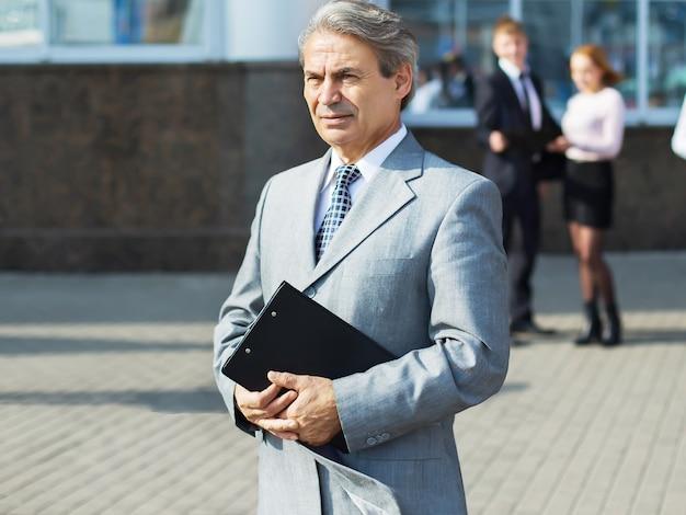 Een succesvolle zakenman met documenten op de achtergrond