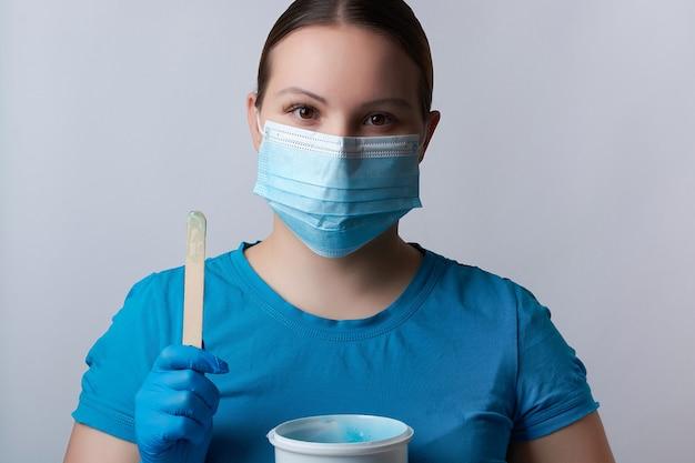 Een suikerende meester in blauwe handschoenen en een medisch masker houdt een stokje blauwe suikerwas vast. ontharing en schoonheidsconcept.