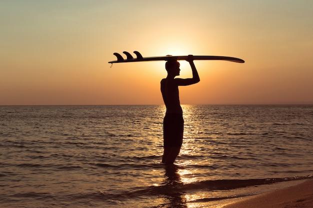 Een surfer bij zonsondergang.