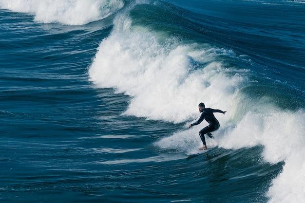 Een surfer man surfen in de zee met prachtige golven