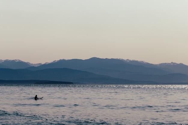 Een surfer met zijn surfplank in het water