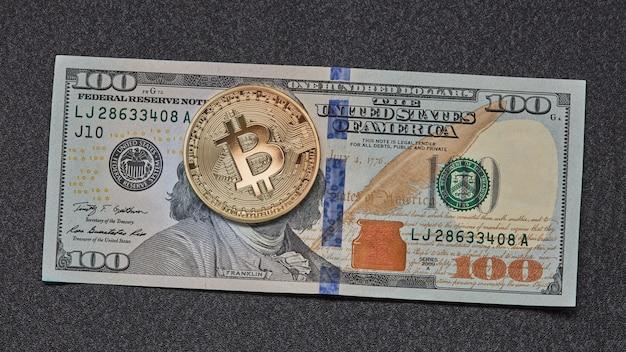Een symbolische munt van bitcoin op bankbiljetten van honderd dollar op donkere achtergrond. wissel bitcoin contant in voor een dollar.