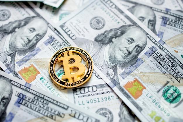 Een symbolische munten van bitcoin op bankbiljetten van honderd dollar. wissel bitcoin cash in voor een dollar.