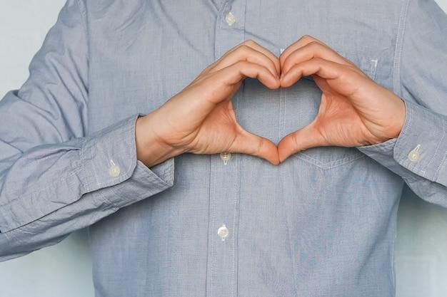 Een symbool van liefde doe handen. valentijnsdag. een verliefde jongeman toont zijn gevoelens. zakenman die een hart maakt met zijn handen op een witte achtergrond, ik hou van zaken. uitdrukking van gevoelens