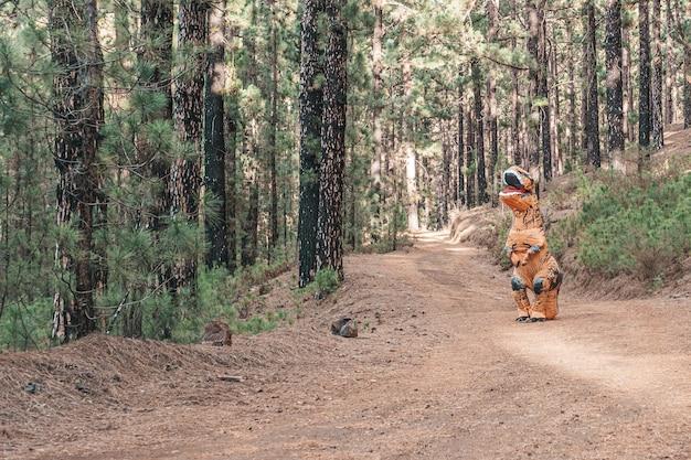 Een t-rex-kostuum dat de aarde ontdekt en op de weg van een bos of berg loopt op zoek naar iets