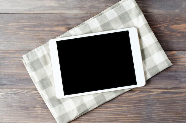 Een tablet-computer en een tafellaken op een bruin houten tafel. kopieer ruimte. concept van het koken van recepten
