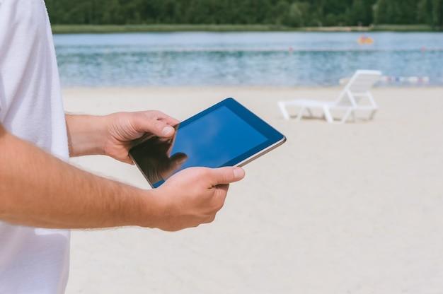 Een tablet in de handen van een man op het strand.