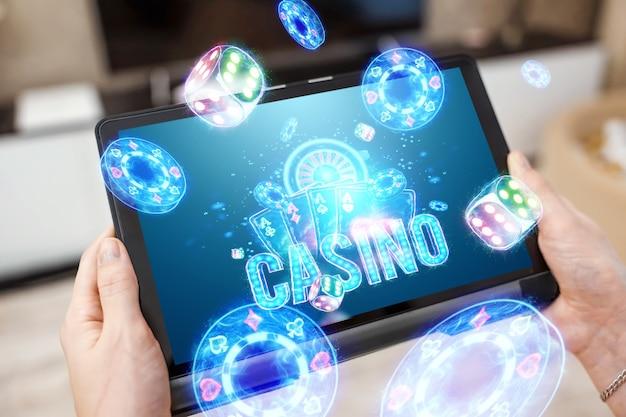 Een tablet in vrouwelijke handen en neon casino reboot, roulette, dobbelstenen, chips. online casino, gokken, internetspellen, wedden. website header, flyer, poster, sjabloon voor reclame.