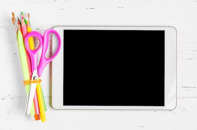 Een tablet met een leeg scherm en kantoorbenodigdheden op een witte houten achtergrond. concept app voor schoolkinderen of online leren voor kinderen. kopieer ruimte